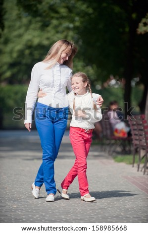 Mother and daughter walking in the summer park - stock photo