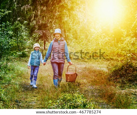 Mother and daughter walking in the woods.