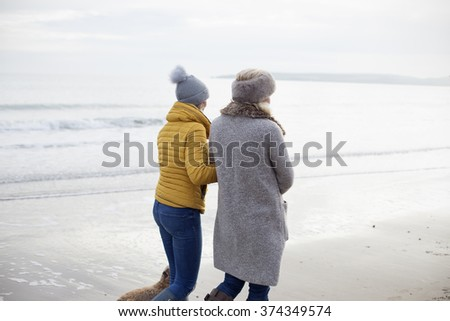 Mother and Daughter walking on beach - stock photo