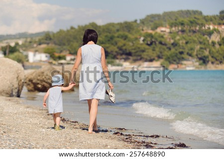 mother and daughter walking on beach at sunny day - stock photo