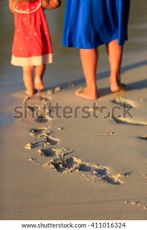 mother and daughter walking on beach leaving footprint in sand - stock photo