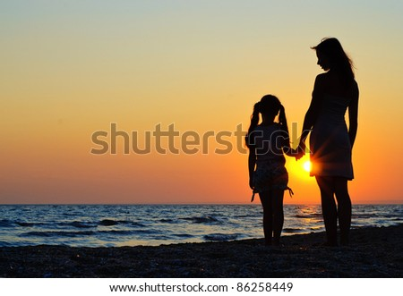 Mother and daughter walking on the beach - stock photo