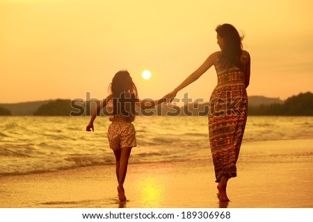 Mother and daughter walking on the beach with sunset - stock photo
