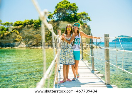Mother and daughter walking on the bridge in a summer tour. Girl on the bridge. girl bent over the railing, girl in sunglasses outdoors
