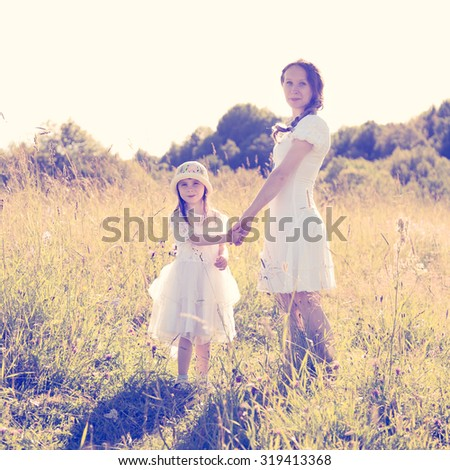 Mother and daughter walking on the sunny meadow. - stock photo