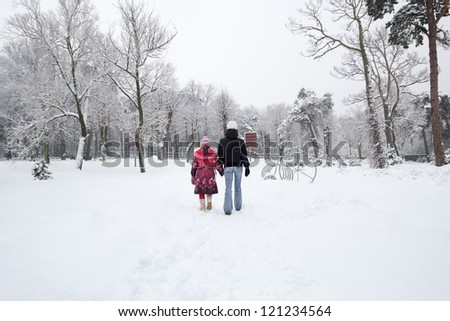 Mother and daughter walking the snowy town park - stock photo