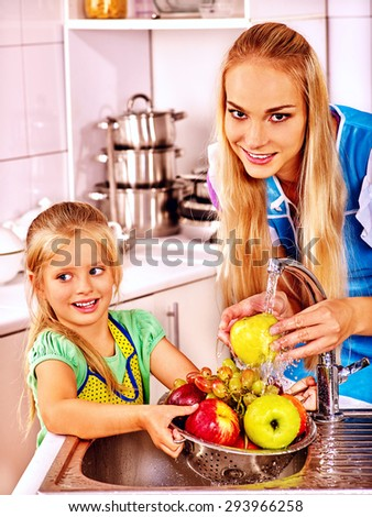 Mother and daughter washing fruit under pouring water at kitchen. - stock photo