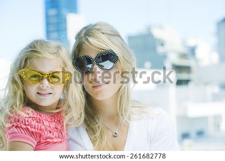 Mother and daughter wearing sunglasses - stock photo