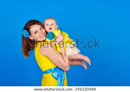 Mother and daughter wearing the same yellow dress. Happy mother holding her daughter in her arms. The concept of a happy family. - stock photo