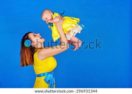 Mother and daughter wearing the same yellow dress. Happy mother picks up her daughter in her arms. The concept of a happy family. - stock photo