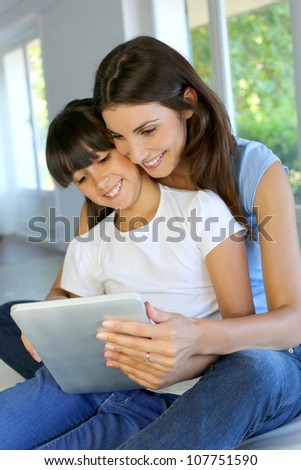 Mother and daughter websurfing on internet with tablet - stock photo