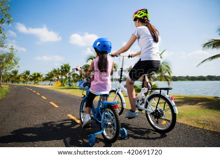 Mother and daughter were cycling at the park in the morning. - stock photo