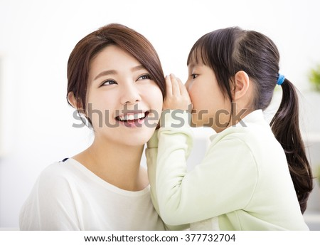mother and daughter whispering gossip - stock photo