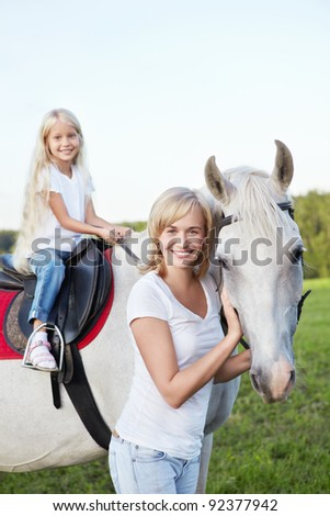 Mother and daughter with a horse - stock photo