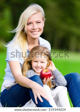 Mother and daughter with apple sitting on the grass embrace each other