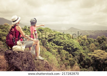 mother and daughter with backpack sitting on the footpath in the mountains at the day time - stock photo