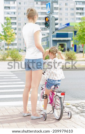 Mother and daughter with bicycle on zebra crossing. - stock photo