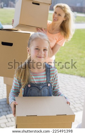 Mother and daughter with cardboard boxes moving into new house - stock photo