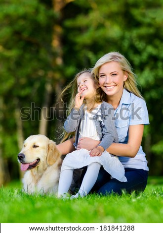 Mother and daughter with dog sitting on the green grass at the summer park - stock photo