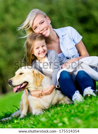 Mother and daughter with golden retriever sitting on the green grass at the summer park