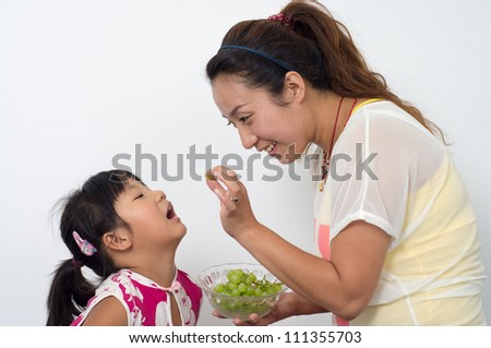 Mother and daughter with grapes.