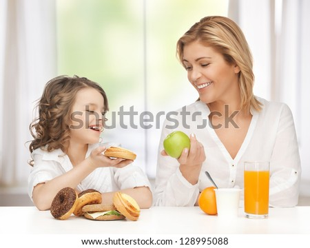 mother and daughter with healthy and unhealthy food - stock photo