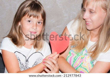 mother and daughter with heart in hands