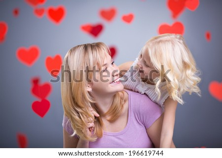 Mother and daughter with hearts in studio - stock photo
