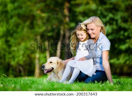 Mother and daughter with labrador sitting on the green grass at the summer park