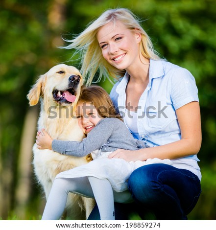 Mother and daughter with pet sitting on the green grass at the summer park - stock photo