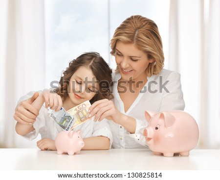 mother and daughter with piggy banks and paper money - stock photo