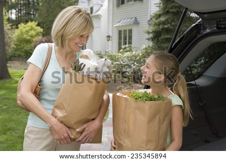 Mother and Daughter with Shopping Bags at Car - stock photo