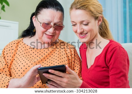 Mother and daughter with tablet computer sitting on the couch. Family smiling and touching the screen. Home interior on the background.