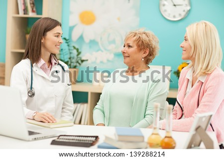 Mother and daughter with their family doctor. - stock photo