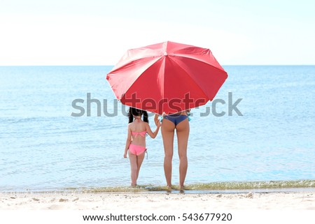 Mother and daughter with umbrella relaxing  on beach