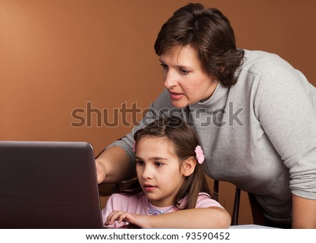 Mother and Daughter work on homework together at the kitchen table - stock photo