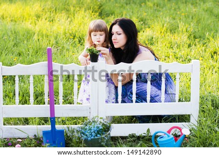 mother and daughter working in flowers garden - stock photo