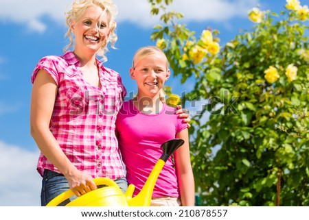 Mother and daughter working in garden watering plants with can in front of rose bushes