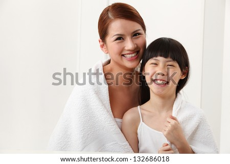 Mother and daughter wrapped in towel - stock photo