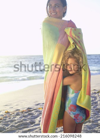 Mother and daughter (5-7) wrapped in towel on beach, smiling, portrait of girl - stock photo