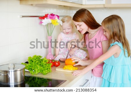 Mother and daughters cooking dinner in a kitchen - stock photo