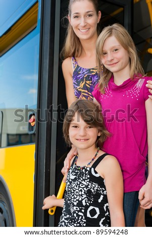 Mother and daughters looking out of a bus; they presumably like to get home - stock photo