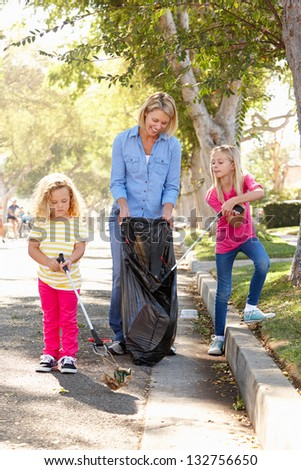 Mother And Daughters Picking Up Litter In Suburban Street - stock photo