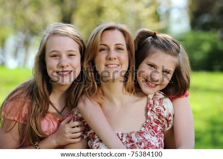 Mother and Daughters portrait outdoors on a sunny day - stock photo