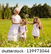 Mother and daughters relaxing on the meadow - stock photo