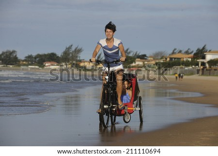 Mother and daughters riding a bike on the beach. - stock photo