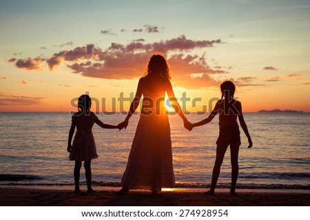 Mother and daughters standing on the beach at the sunset time. Concept of friendly family. - stock photo