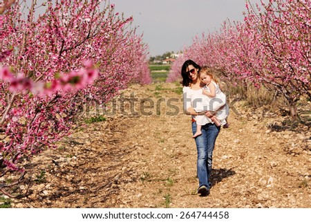 mother and daughters walking together in the park - stock photo