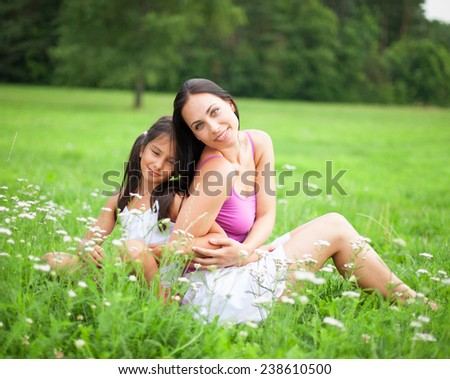 Mother and daugter sitting in flower meadow