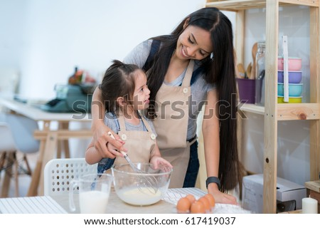 mother and daugthter cooking togather for make bread for dinner, in kitchen room, kid, children
